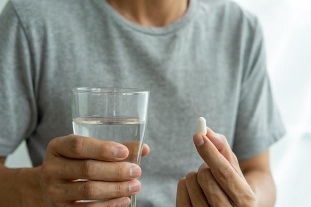 Der mann der hand, der ein nahrungsergänzungsmittel oder ein medikament oder ein vitamin und ein glas wasser zur einnahme bereithält. gesundheitswesen, medizin, selbstversorgung, krankheit und apothekenkonzept.
