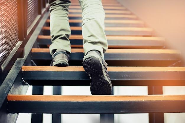 Der mann, der herauf die treppe mit sonnensporthintergrund geht.