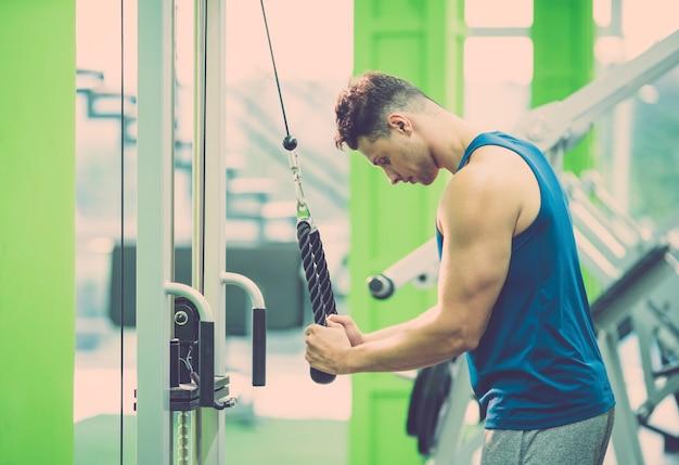 Der mann, der im fitnessclub mit einem seil trainiert