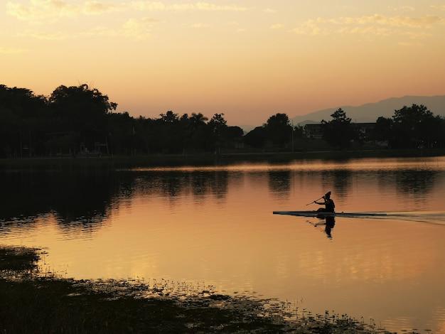 Der mann, der kajak trainiert, segelt im flusssonnenuntergang