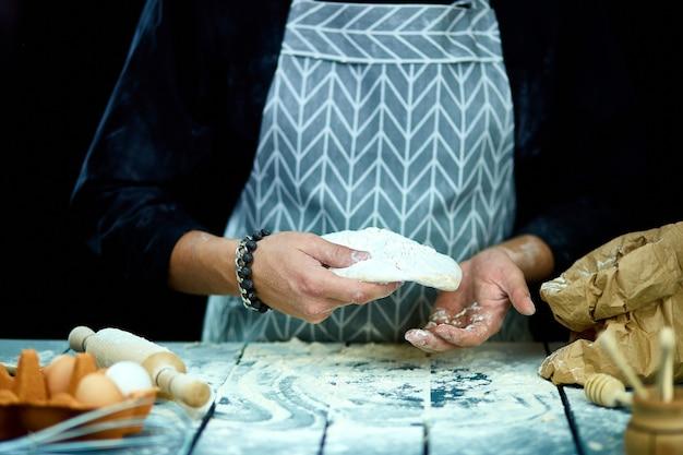 Der mann, der koch kocht, wirft den teig, fliegt, friert in bewegung.