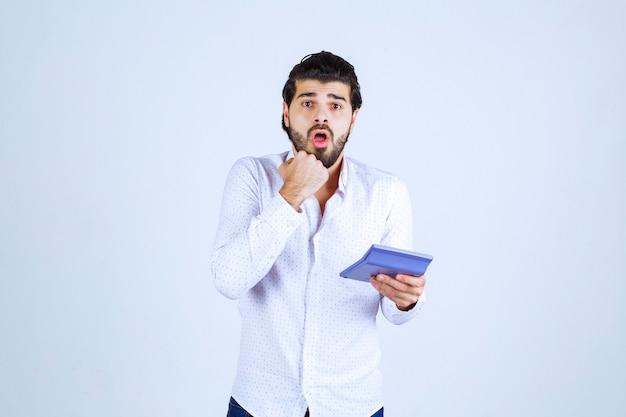 Der mann, der mit dem taschenrechner arbeitet, sieht verwirrt und nachdenklich aus.