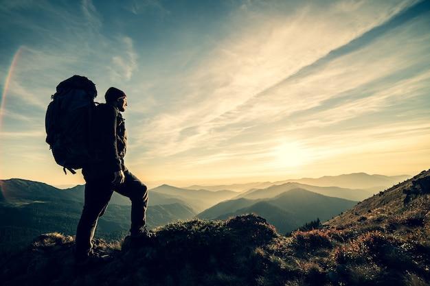 Der mann, der mit einem campingrucksack auf einem felsen mit einem malerischen sonnenuntergang steht