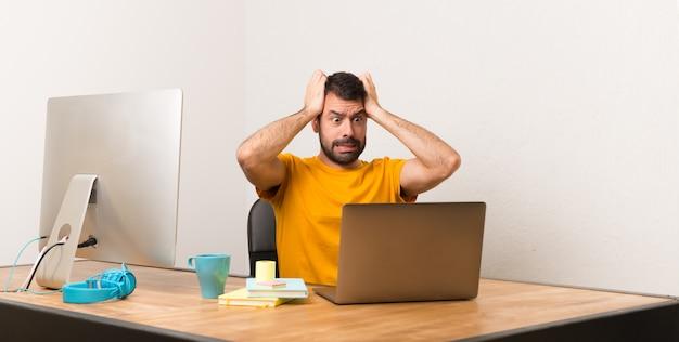 Der mann, der mit laptot in einem büro arbeitet, nimmt hände am kopf, weil migräne hat