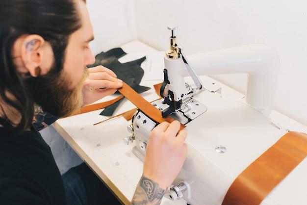 Der mann, der mit leder arbeitet, verarbeitet das leder mit einer speziellen maschine