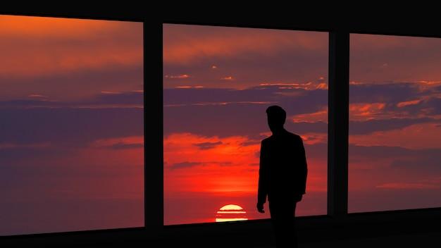 Der mann, der nahe dem panoramafenster auf dem schönen sonnenunterganghintergrund steht