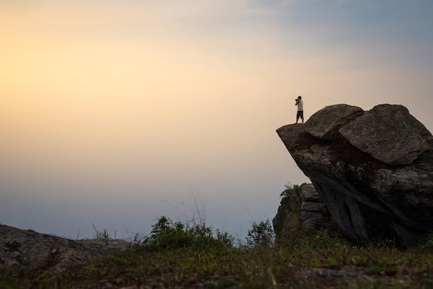 Der mann, der steht und foto auf klippe macht. ein mann steht auf einem felsvorsprung.