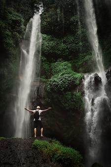 Der mann, der wasserfall genießt, hob hände an. reisen lifestyle und erfolgskonzept urlaub in die wilde natur auf berg und regenwald.