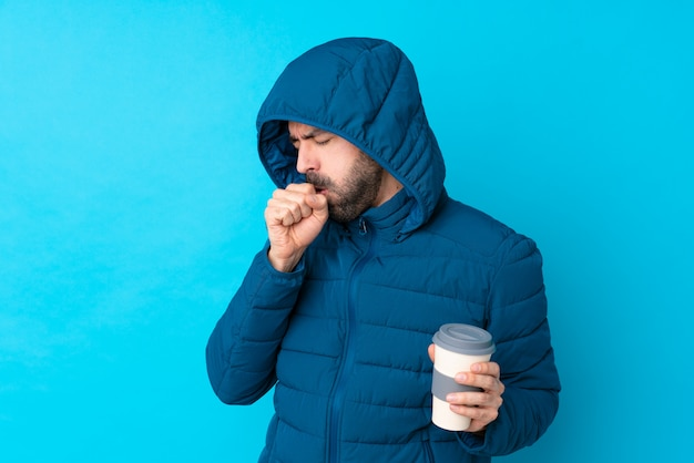 Der mann, der winterjacke trägt und einen mitnehmerkaffee über lokalisierter blauer wand hält, leidet mit husten und fühlt sich schlecht