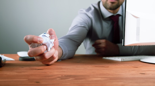 Der mann drückte das papier zu einer kugel zusammen.