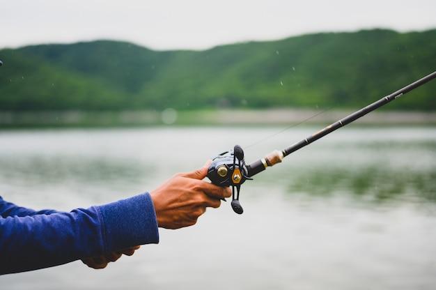 Der mann eines fischers fischt an einem natürlichen see