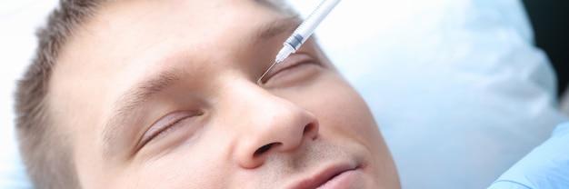 Der mann erhält eine verjüngende injektion in sein gesicht schönheitsinjektionen für das konzept der männer