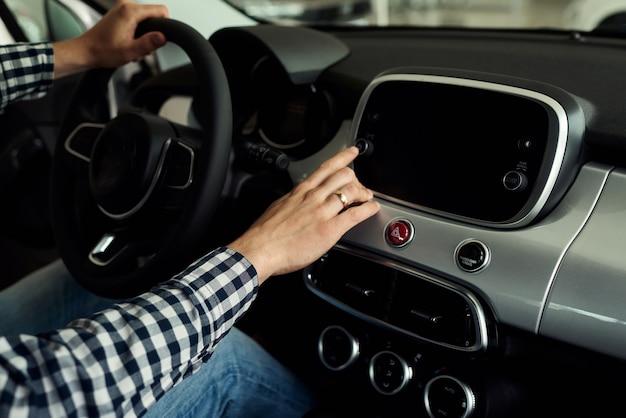 Der mann erwägt eine neue modellpalette von autos und versucht, das beste für sich auszuwählen.
