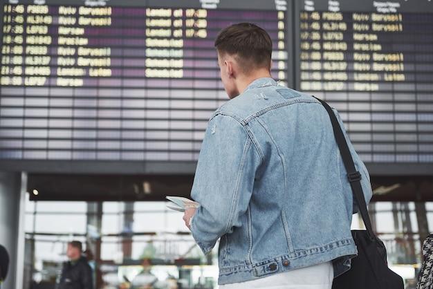 Der mann erwartet seinen flug am flughafen.