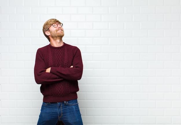 Der mann fühlt sich glücklich, stolz und hoffnungsvoll, wundert sich oder denkt nach und schaut auf, um den raum mit verschränkten armen zu kopieren