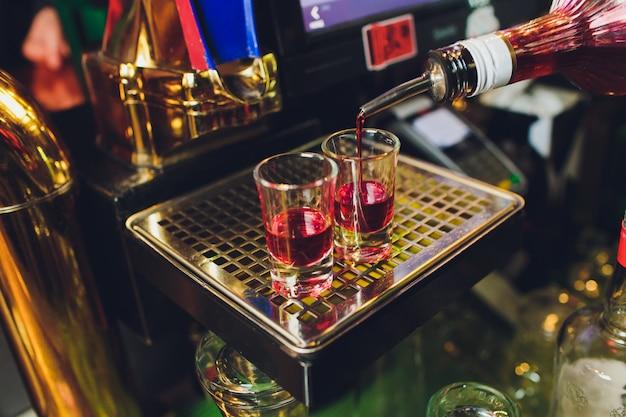 Der mann gießt etwas brandy in ein glas hinter der bar.