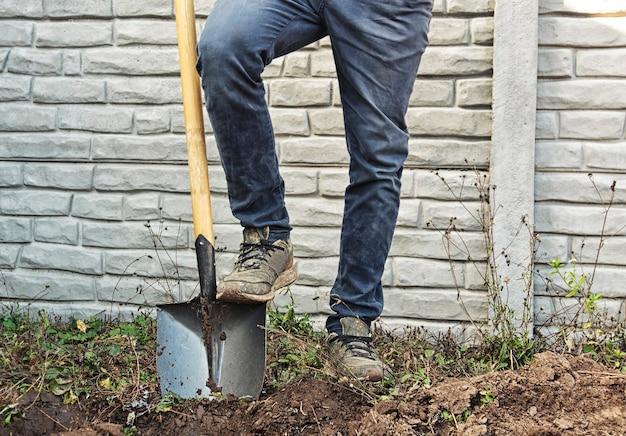 Der mann gräbt den boden seines landhauses