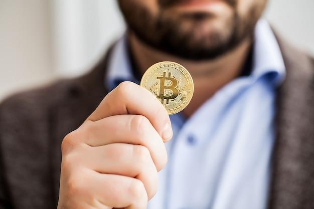 Der mann hält bitcoins in seinem büro