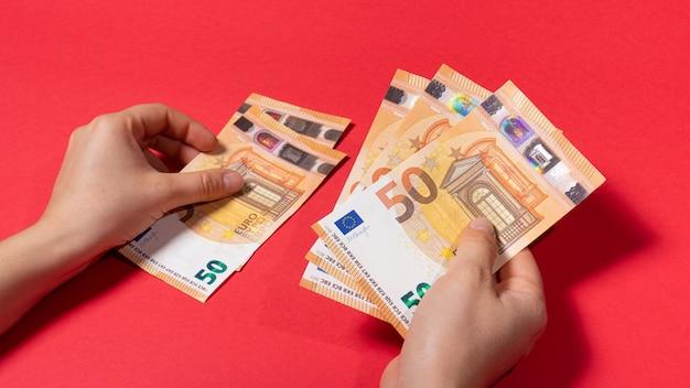 Der mann hält das geld der banknote für 50 euro auf rotem grund.