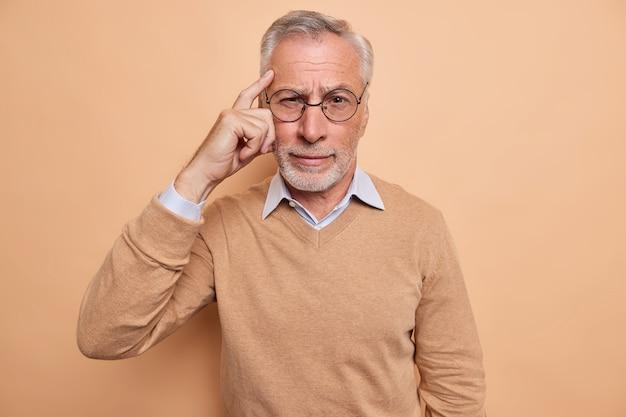 Der mann hält den finger auf die schläfe und versucht, sich an etwas zu erinnern, das sich auf die kamera konzentriert, trägt eine brille, einen lässigen pullover, isoliert auf braun