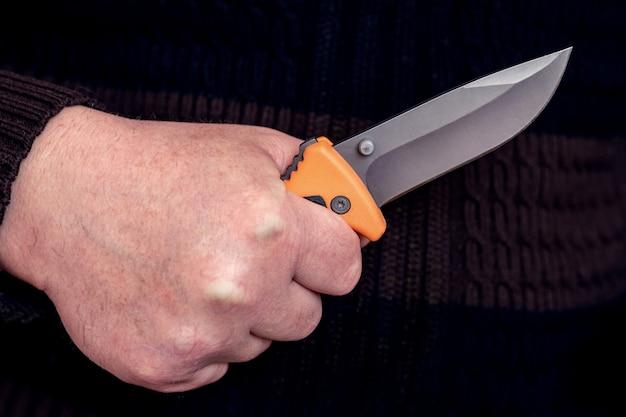 Der mann hält ein jagdmesser. ein messer in der hand eines mannes zum angriff oder zur verteidigung
