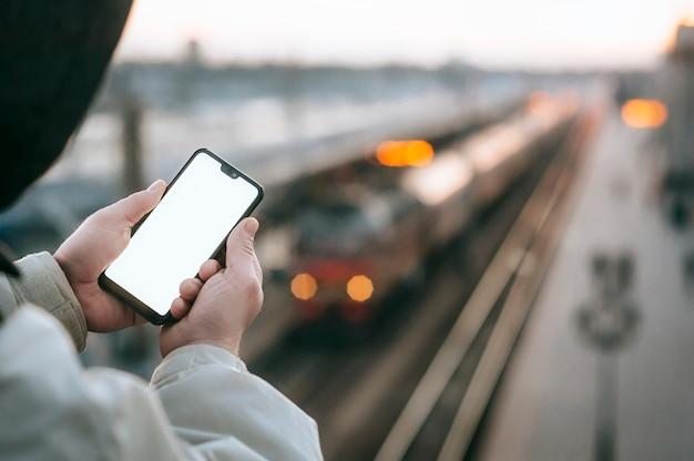 Der mann hält ein modell-smartphone in der hand