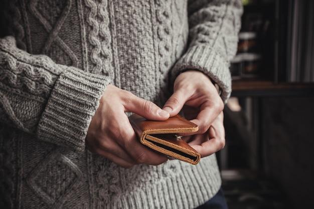 Der mann hält eine braune lederbrieftasche