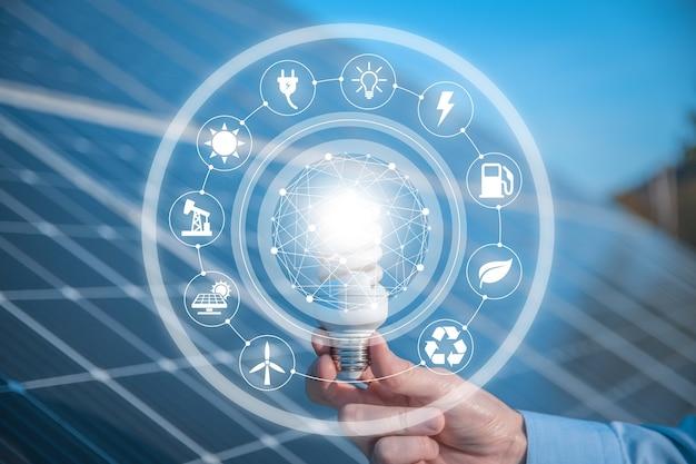 Der mann hält eine glühbirne, led-birne auf sonnenkollektoren mit symbolen energiequellen für erneuerbare, nachhaltige entwicklung. ökologie-konzept.