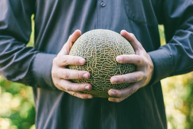 Der mann hält eine reife melone