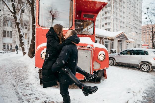 Der mann hält sein geliebtes mädchen vor dem hintergrund eines roten busses in den armen