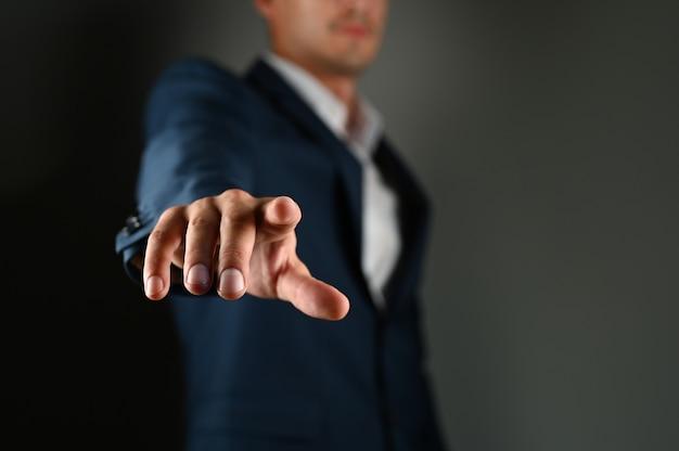 Der mann hält seinen zeigefinger vor sich. ein mann im anzug zeigt mit dem finger nach vorne auf ein schwarzes feld. konzept: klicken sie auf die schaltfläche, geben sie spezifizieren an. hochwertiges foto