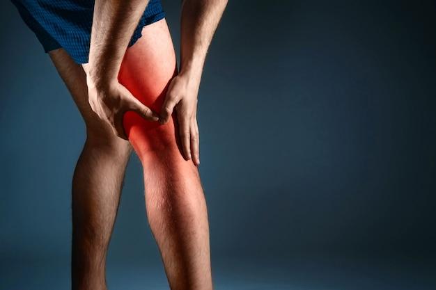 Der mann hält sich am knie fest, der schmerz im knie