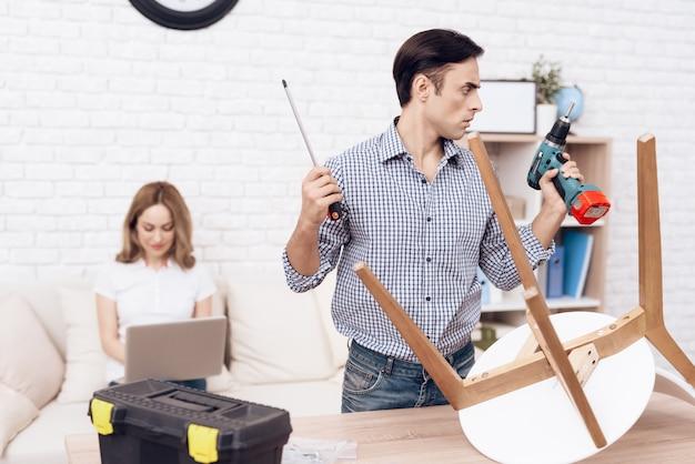 Der mann handwerker beschäftigt sich mit der montage des stuhls.