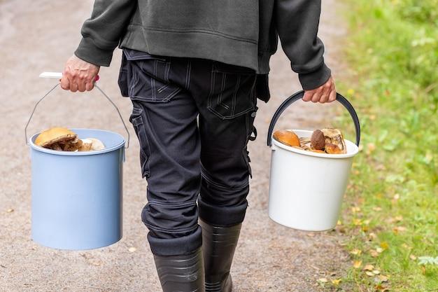 Der mann hat eimer voller pilze in den händen sammeln und pilzvorräte für den winter