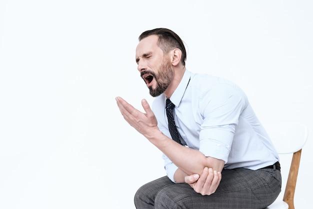 Der mann hat einen schmerzenden ellbogen. es tut ihm weh, er leidet.