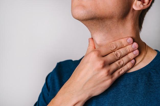 Der mann hat halsschmerzen und überprüft die mandeln und lymphknoten