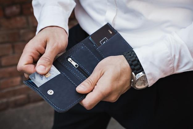Der mann holt eine kreditkarte heraus