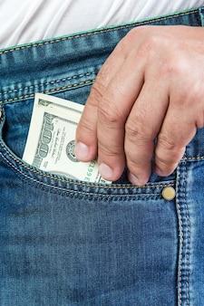 Der mann holt seine jeans-dollars aus der tasche
