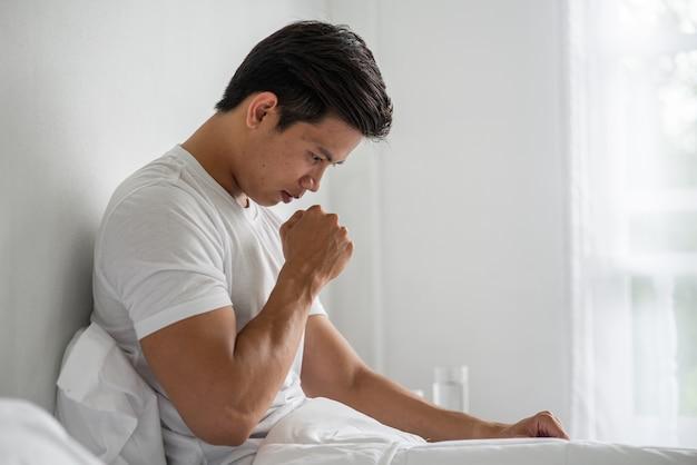 Der mann hustete und legte seine hand über seinen mund und setzte sich auf das bett.
