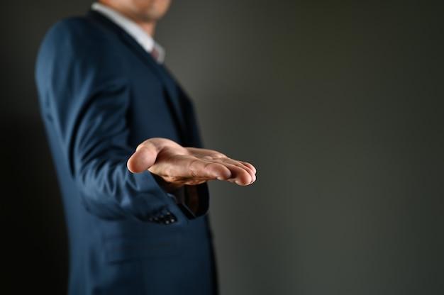 Der mann im anzug streckt die handfläche aus. hochwertiges foto