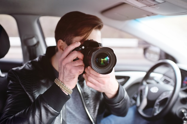 Der mann im auto überprüft die fotos auf der kamera. spion, paparazzi, journalist, fotograf.