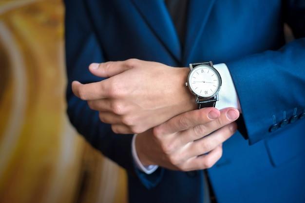 Der mann im blauen anzug schaut auf die uhr