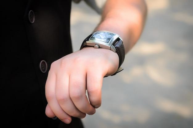 Der mann im braunen anzug schaut auf seine uhr, handuhr