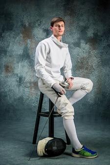 Der mann im fechtanzug mit schwert gegen grau