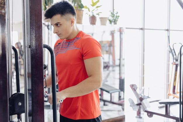Der mann im fitnessstudio wiegt die arme im simulator