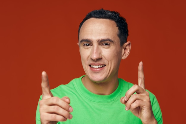 Der mann im grünen t-shirt zeigt nach oben