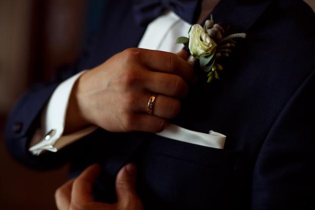 Der mann im schwarzen anzug und weißem hemd korrigiert den boutonniere hautnah. hand einen bräutigam mit einem schmetterling und boutonniere. hansome kerl im dunklen anzug und weißem hemd korrigiert boutonniere