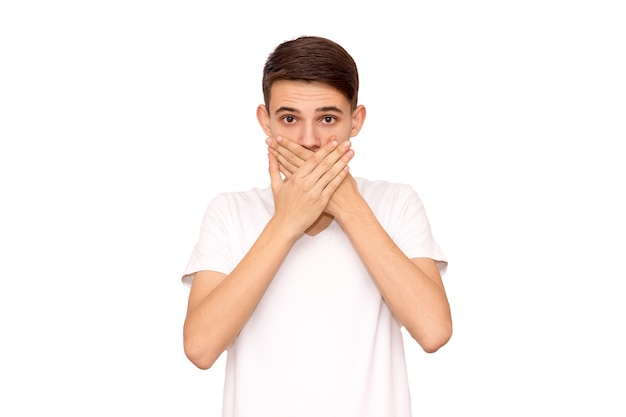 Der mann im weißen t-shirt bedeckt den mund mit den händen und dem isolat