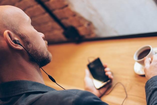 Der mann in den kopfhörern unter verwendung des handys, sitzend mit kaffee am café