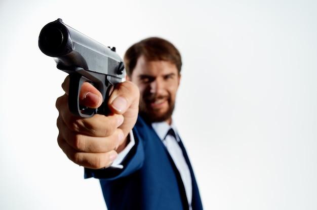 Der mann in einem anzug mit einer pistole in der hand kriminaldetektivmörder heller hintergrund